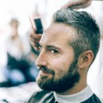 grey haired beautiful bearded man in barber shop receiving hair cut